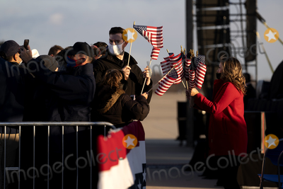 American Flag Photo - American flags are passed out to supporters of US President Donald Trump prior to a farewell ceremony at Joint Base Andrews Maryland US on Wednesday Jan 20 2021 Trump departs Washington with Americans more politically divided and more likely to be out of work than when he arrived while awaiting trial for his second impeachment - an ignominious end to one of the most turbulent presidencies in American history Photographer Stefani ReynoldsBloombergAdMedia