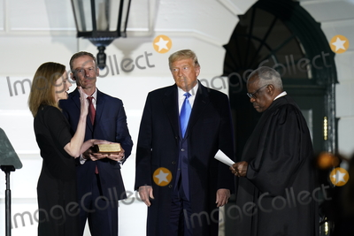 Supreme Court Photo - Associate Justice of the Supreme Court Clarence Thomas administers the oath of office to Judge Amy Coney Barrett to be Associate Justice of the Supreme Court on the South Lawn of the White House in Washington DC on Monday October 26 2020  US President Donald J Trump and her husband Jesse M Barrett look onCredit Chris Kleponis  Pool via CNPAdMedia
