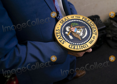 Seal Photo - Communications staff carries away the presidential seal after President Donald Trump delivered remarks on the stock marked and the Dow reaching 30000 for the first time in history at the White House in Washington DC on Tuesday November 24 2020 Credit Kevin Dietsch  Pool via CNPAdMedia