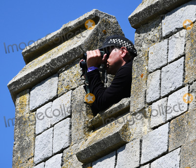 Police Officer Photo - 19 May 2018 - A police officer looks through Binoculars at St Georges Chapel at Windsor Castle for the wedding of Meghan Markle and Prince Harry Photo Credit ALPRAdMedia