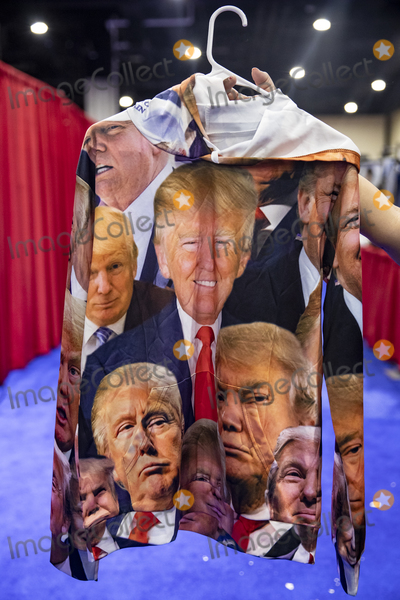 The Faces Photo - OXON HILL Md - FEBRUARY 27 A booth worker holds up a sweat shirt plastered with the face of US President Donald Trump that is for sale at the Conservative Political Action Conference CPAC 2020 in Oxon Hill Md on Thursday February 27 2020Credit Samuel Corum  CNPAdMedia