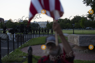 The National Photo - A demonstrator holds an American flag as the National Guard looks on at protestors gathered outside the White House in Washington DC US on Sunday May 31 2020 following the death of an unarmed black man at the hands of Minnesota police on May 25 2020  Credit Stefani Reynolds  CNPAdMedia