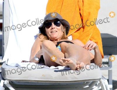 Claire Chazal Photo - French journalist romance writer and director of news at TF1 Claire Chazal wears a black bikini as she relaxes on the beach during a winter holiday with husband Arnaud Lemaire Chazal who also presents Jenous de Claire on gay network Pink TV took a stroll on the beach and seemed to be enjoying the warm South Florida sun as she lounged beachside with Lemaire Miami Beach FL 122110