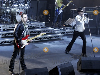 JD Fortune Photo - INXS  guitaristsaxophonist Kirk Pengilly (L) and the bands new lead singer JD Fortune performing onstage at