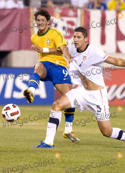 Alexandre Pato Photo - Brazil forward Alexandre Pato (L) shoots on goal while US defender Omar Gonzalez (R) tries to stop him during the US vs Brazil game at the New Meadowlands Stadium on August 10 2010 in East Rutherford New Jersey