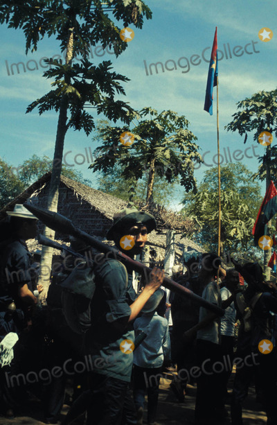 Jeff Taylor Photo - Vietcong Soldier with B-40 Anti-tank Rocket Greande Stands with Others Waving the Nlf Flag in Village Mekong Delta Photo by Jeff TaylorGlobe Photos