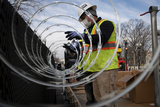 Photo - A crew installs concertina wire atop the tall barricades which surround the US Capitol as preparations are made for the upcoming inauguration President Joe Biden at the US Capitol in Washington DC Friday January 15 2021 Credit Rod Lamkey  CNPAdMedia