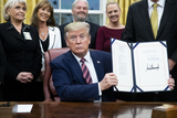Photo - US President Donald J Trump signs a bill during a ceremony in the Oval Office of the White House